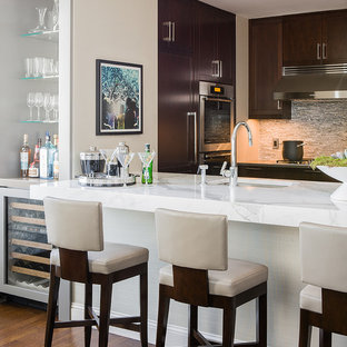 Example of a large trendy kitchen design in Boston with stainless steel appliances, shaker cabinets, dark wood cabinets, marble countertops, gray backsplash, glass tile backsplash and an island
