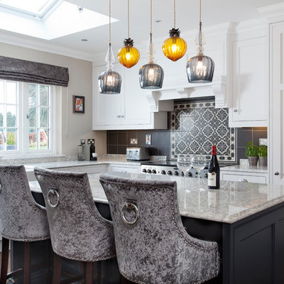 Trendy l-shaped dark wood floor and brown floor kitchen photo in Dublin with a farmhouse sink, shaker cabinets, white cabinets, gray backsplash, mosaic tile backsplash, an island and gray countertops