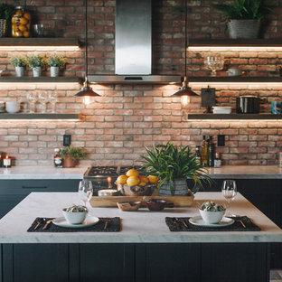ロサンゼルスの大きいインダストリアルスタイルのおしゃれなキッチン (エプロンフロントシンク、シェーカースタイル扉のキャビネット、黒いキャビネット、赤いキッチンパネル、レンガのキッチンパネル、シルバーの調理設備の、ラミネートの床、茶色い床、白いキッチンカウンター) の写真