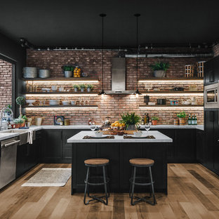 This is an example of a large industrial u-shaped eat-in kitchen in Los Angeles with laminate floors, a farmhouse sink, shaker cabinets, black cabinets, red splashback, brick splashback, stainless steel appliances, with island, brown floor and white benchtop.