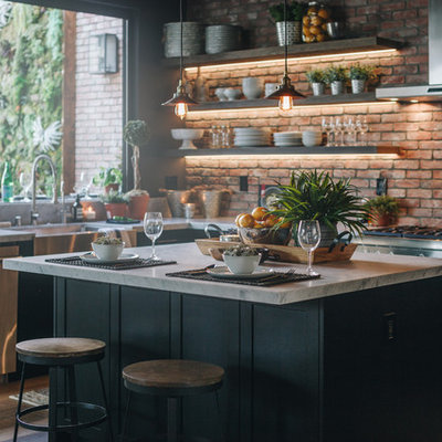 Large urban l-shaped laminate floor and brown floor eat-in kitchen photo in Los Angeles with a farmhouse sink, shaker cabinets, black cabinets, red backsplash, brick backsplash, stainless steel appliances, an island and white countertops