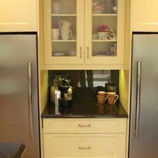 他の地域の中サイズのトラディショナルスタイルのおしゃれなキッチン (アンダーカウンターシンク、落し込みパネル扉のキャビネット、黄色いキャビネット、御影石カウンター、緑のキッチンパネル、石スラブのキッチンパネル、シルバーの調理設備の、セラミックタイルの床、緑の床、緑のキッチンカウンター) の写真