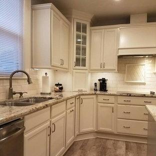 ローリーの中サイズのトラディショナルスタイルのおしゃれなキッチン (アンダーカウンターシンク、フラットパネル扉のキャビネット、ベージュのキャビネット、御影石カウンター、ベージュキッチンパネル、磁器タイルのキッチンパネル、シルバーの調理設備の、クッションフロア) の写真
