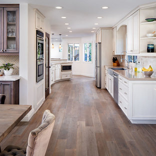 Inspiration for a large mediterranean galley kitchen/diner in San Diego with a belfast sink, beaded cabinets, beige cabinets, limestone worktops, beige splashback, stone tiled splashback, stainless steel appliances, medium hardwood flooring and a breakfast bar.
