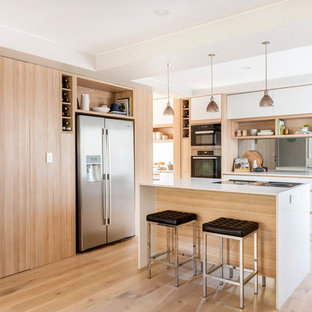 Photo of a mid-sized contemporary l-shaped open plan kitchen in Perth with light wood cabinets, an island, an undermount sink, flat-panel cabinets, mirror splashback, stainless steel appliances and light hardwood floors.