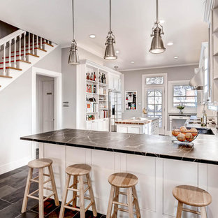 Design ideas for a large transitional l-shaped open plan kitchen in Denver with a farmhouse sink, recessed-panel cabinets, white cabinets, soapstone benchtops, grey splashback, subway tile splashback, stainless steel appliances, ceramic floors and with island.