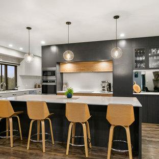Moderne Küche mit Einbauwaschbecken, flächenbündigen Schrankfronten, schwarzen Schränken, Küchenrückwand in Weiß, Rückwand aus Spiegelfliesen, braunem Holzboden, Kücheninsel, braunem Boden und gelber Arbeitsplatte in Sonstige