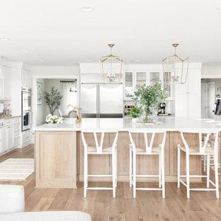 Skandinavisk inredning av ett stort vit vitt kök, med en rustik diskho, luckor med infälld panel, vita skåp, bänkskiva i kvartsit, vitt stänkskydd, stänkskydd i marmor, rostfria vitvaror, ljust trägolv, en köksö och beiget golv