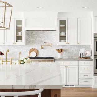 Ispirazione per una grande cucina a L scandinava con lavello stile country, ante bianche, paraspruzzi bianco, elettrodomestici in acciaio inossidabile, isola, ante con riquadro incassato, top in quarzite, paraspruzzi in marmo, parquet chiaro, pavimento beige e top bianco
