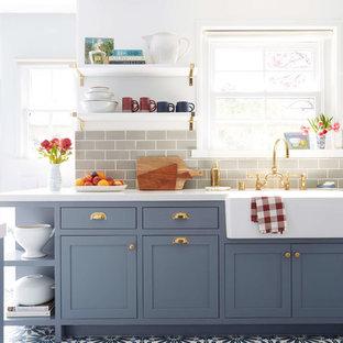 Bild på ett vintage kök, med blå skåp, grått stänkskydd, stänkskydd i keramik, en rustik diskho, skåp i shakerstil och cementgolv