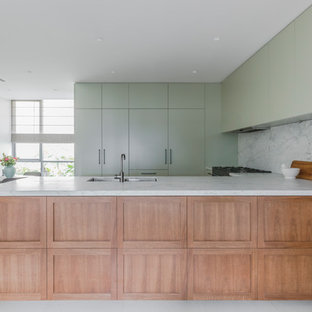 Inspiration for a mid-sized contemporary u-shaped open plan kitchen in Sydney with an undermount sink, marble benchtops, white splashback, marble splashback, black appliances, porcelain floors, white floor, white benchtop, flat-panel cabinets, green cabinets and a peninsula.