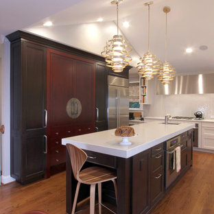 Mid-sized eclectic eat-in kitchen inspiration - Mid-sized eclectic u-shaped medium tone wood floor eat-in kitchen photo in Raleigh with a single-bowl sink, recessed-panel cabinets, dark wood cabinets, quartz countertops, yellow backsplash, glass tile backsplash, stainless steel appliances and an island