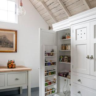 Country Küche mit Vorratsschrank, Kassettenfronten, weißen Schränken und gebeiztem Holzboden in Sussex