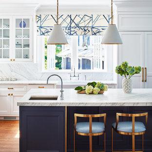 ニューヨークの広いトランジショナルスタイルのおしゃれなキッチン (白いキャビネット、白いキッチンパネル、無垢フローリング、白いキッチンカウンター、エプロンフロントシンク、シェーカースタイル扉のキャビネット、大理石カウンター、大理石のキッチンパネル、パネルと同色の調理設備) の写真