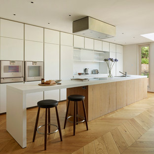 Inspiration for a modern galley kitchen in London with a submerged sink, white splashback, integrated appliances, light hardwood flooring, flat-panel cabinets, white cabinets and an island.