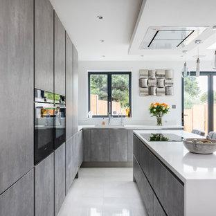 Foto de cocina comedor contemporánea, de tamaño medio, con armarios con paneles lisos, puertas de armario con efecto envejecido, encimera de cuarcita, electrodomésticos con paneles, una isla y suelo blanco