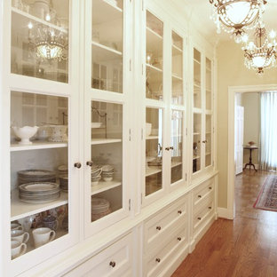 Design ideas for a large classic galley kitchen pantry in St Louis with glass-front cabinets, white cabinets, marble worktops, white splashback, integrated appliances and medium hardwood flooring.