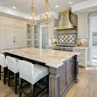 Tuscan light wood floor and beige floor kitchen photo in Los Angeles with shaker cabinets, beige cabinets, gray backsplash, subway tile backsplash, stainless steel appliances, an island and multicolored countertops