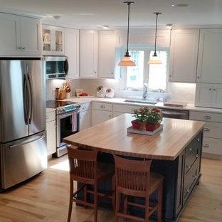 シャーロットの中サイズのシャビーシック調のおしゃれなキッチン (ドロップインシンク、落し込みパネル扉のキャビネット、クオーツストーンカウンター、白いキッチンパネル、サブウェイタイルのキッチンパネル、シルバーの調理設備、淡色無垢フローリング) の写真