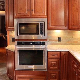 ニューヨークの中サイズのトラディショナルスタイルのおしゃれなキッチン (エプロンフロントシンク、レイズドパネル扉のキャビネット、中間色木目調キャビネット、クオーツストーンカウンター、茶色いキッチンパネル、スレートのキッチンパネル、シルバーの調理設備、クッションフロア、マルチカラーの床、ベージュのキッチンカウンター) の写真