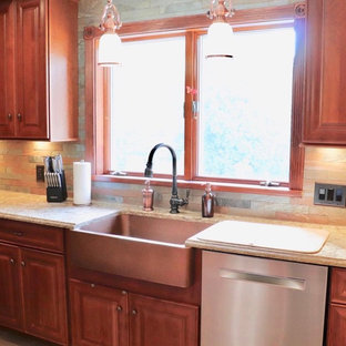 This is an example of a mid-sized traditional u-shaped separate kitchen in New York with a farmhouse sink, raised-panel cabinets, medium wood cabinets, quartz benchtops, brown splashback, slate splashback, stainless steel appliances, vinyl floors, with island, multi-coloured floor and beige benchtop.