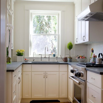Example of a small classic enclosed kitchen design in Boston with stainless steel appliances, recessed-panel cabinets, white cabinets and white backsplash