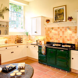 Example of a cottage terra-cotta floor eat-in kitchen design in Other with shaker cabinets, white cabinets, wood countertops, a farmhouse sink, orange backsplash and colored appliances