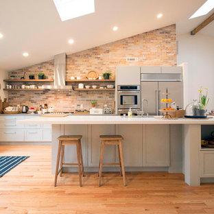 サンフランシスコの中サイズのカントリー風おしゃれなキッチン (アンダーカウンターシンク、シェーカースタイル扉のキャビネット、グレーのキャビネット、オレンジのキッチンパネル、レンガのキッチンパネル、シルバーの調理設備の、無垢フローリング、茶色い床、白いキッチンカウンター、人工大理石カウンター) の写真