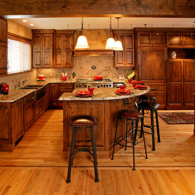 Example of a mountain style kitchen design in Denver with a farmhouse sink, raised-panel cabinets, medium tone wood cabinets, beige backsplash and paneled appliances