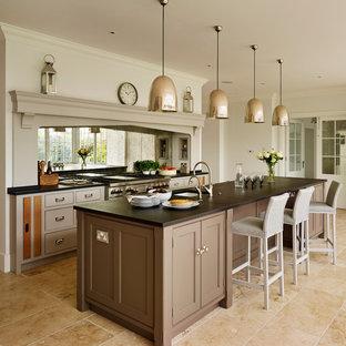 エセックスの巨大なトラディショナルスタイルのおしゃれなキッチン (エプロンフロントシンク、フラットパネル扉のキャビネット、グレーのキャビネット、珪岩カウンター、メタリックのキッチンパネル、ミラータイルのキッチンパネル、シルバーの調理設備、ライムストーンの床) の写真
