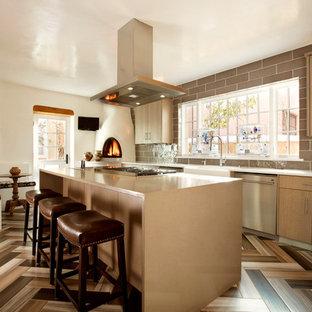 アルバカーキの中くらいのサンタフェスタイルのおしゃれなキッチン (エプロンフロントシンク、フラットパネル扉のキャビネット、中間色木目調キャビネット、クオーツストーンカウンター、グレーのキッチンパネル、セラミックタイルのキッチンパネル、シルバーの調理設備、磁器タイルの床) の写真