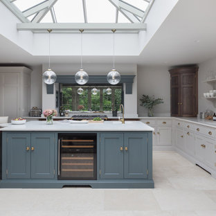 This is an example of a medium sized classic l-shaped kitchen in Essex with a submerged sink, shaker cabinets, grey cabinets, mirror splashback, stainless steel appliances, an island, beige floors and white worktops.
