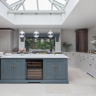 Mittelgroße Klassische Küche in L-Form mit Unterbauwaschbecken, Schrankfronten im Shaker-Stil, grauen Schränken, Rückwand aus Spiegelfliesen, Küchengeräten aus Edelstahl, Kücheninsel, beigem Boden und weißer Arbeitsplatte in Essex