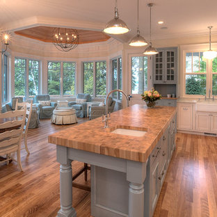Coastal open concept kitchen designs - Inspiration for a coastal open concept kitchen remodel in Other with a farmhouse sink, blue cabinets and wood countertops