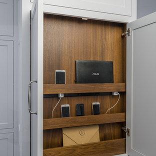 Klassisk inredning av ett avskilt, mellanstort l-kök, med en integrerad diskho, luckor med infälld panel, vita skåp, bänkskiva i täljsten, flerfärgad stänkskydd, stänkskydd i porslinskakel, rostfria vitvaror, mörkt trägolv, en köksö och brunt golv