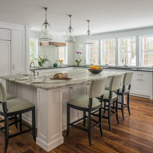 This is an example of a mid-sized transitional l-shaped separate kitchen in Boston with an integrated sink, recessed-panel cabinets, white cabinets, soapstone benchtops, multi-coloured splashback, porcelain splashback, stainless steel appliances, dark hardwood floors, with island and brown floor.
