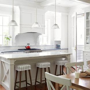 Свежая идея для дизайна: кухня в стиле кантри с обеденным столом, раковиной в стиле кантри, белыми фасадами, гранитной столешницей, белым фартуком, фартуком из плитки кабанчик, техникой из нержавеющей стали, паркетным полом среднего тона, островом, фасадами в стиле шейкер и оранжевым полом - отличное фото интерьера