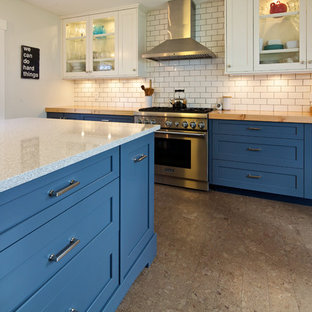 Photo of a mid-sized country l-shaped open plan kitchen in Vancouver with a farmhouse sink, shaker cabinets, blue cabinets, quartzite benchtops, white splashback, subway tile splashback, stainless steel appliances, cork floors and with island.