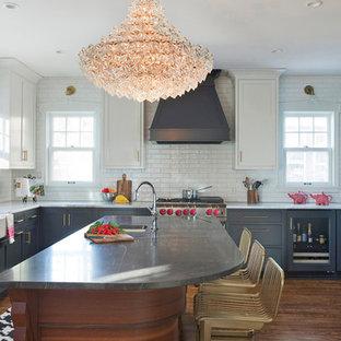 ミネアポリスのエクレクティックスタイルのおしゃれなキッチン (グレーのキャビネット、大理石カウンター、エプロンフロントシンク、白いキッチンパネル、サブウェイタイルのキッチンパネル、無垢フローリング、茶色い床、落し込みパネル扉のキャビネット、グレーのキッチンカウンター) の写真
