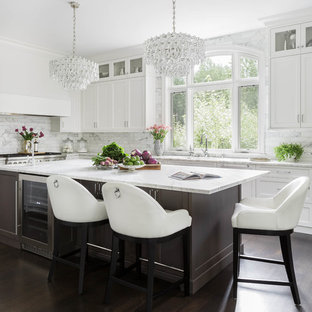 Large transitional kitchen designs - Example of a large transitional u-shaped dark wood floor and brown floor kitchen design in Seattle with an undermount sink, shaker cabinets, white cabinets, marble countertops, white backsplash, marble backsplash, stainless steel appliances and an island
