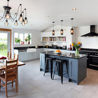Design ideas for a large traditional u-shaped kitchen/diner in Manchester with a belfast sink, shaker cabinets, white splashback, metro tiled splashback, black appliances and an island.