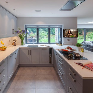 Medium sized traditional u-shaped open plan kitchen in Surrey with shaker cabinets, grey cabinets, composite countertops, white splashback, porcelain flooring, a breakfast bar, grey floors, a submerged sink and black appliances.