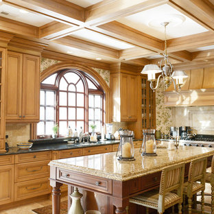 This is an example of a traditional l-shaped kitchen in New York with raised-panel cabinets, medium wood cabinets, beige splashback, stainless steel appliances and with island.