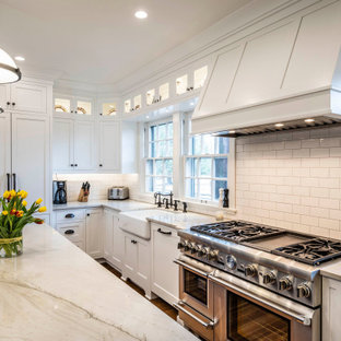 Kitchen pantry - mid-sized transitional u-shaped medium tone wood floor and brown floor kitchen pantry idea in Indianapolis with a farmhouse sink, shaker cabinets, white cabinets, quartz countertops, white backsplash, porcelain backsplash, paneled appliances, an island and white countertops