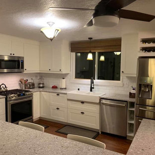 Mid-sized traditional eat-in kitchen designs - Mid-sized elegant u-shaped laminate floor and brown floor eat-in kitchen photo in Other with a double-bowl sink, shaker cabinets, white cabinets, quartzite countertops, white backsplash, subway tile backsplash, stainless steel appliances, a peninsula and gray countertops
