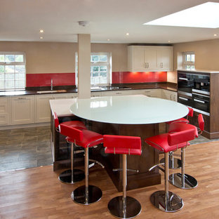 Large traditional open concept kitchen pictures - Large elegant u-shaped open concept kitchen photo in London with an integrated sink, shaker cabinets, white cabinets, glass countertops, red backsplash, glass sheet backsplash, stainless steel appliances and a peninsula