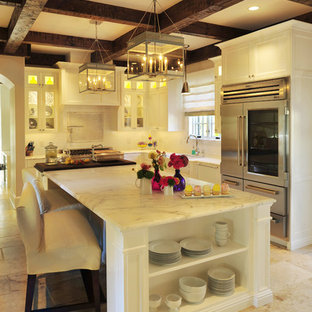 Traditional kitchen pictures - Example of a classic l-shaped kitchen design in Nashville with glass-front cabinets, white cabinets, marble countertops and stainless steel appliances