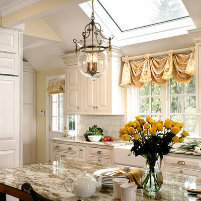 Kitchen - mid-sized traditional l-shaped dark wood floor and brown floor kitchen idea in New York with a farmhouse sink, raised-panel cabinets, white backsplash, white cabinets, marble countertops, subway tile backsplash, paneled appliances and an island