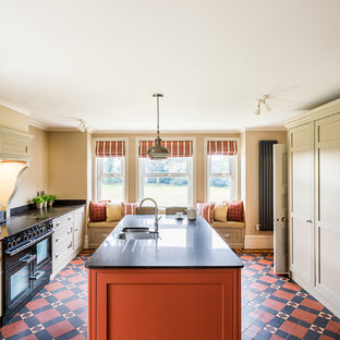 Mid-sized traditional kitchen in Cheshire with a double-bowl sink, recessed-panel cabinets, granite benchtops, orange splashback, glass sheet splashback, black appliances, cement tiles, with island and multi-coloured floor.