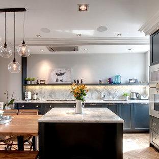 Exempel på ett mellanstort modernt kök med öppen planlösning, med skåp i shakerstil, blå skåp, en köksö, en undermonterad diskho, granitbänkskiva, mellanmörkt trägolv, stänkskydd i sten och integrerade vitvaror